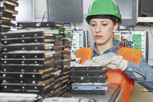 Female worker in computer recycling plat sorting hard disks - RKNF00420