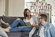 Smiling couple relaxing together in the living room - FMKF03136