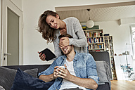 Woman surprising her boyfriend sitting on the couch in the living room - FMKF03145