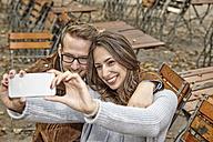 Happy couple taking selfie with smartphone in autumnal beer garden - FMKF03157