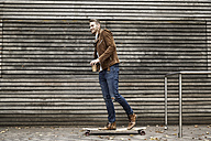 Smiling man with coffee to go on skateboard in front of wooden wall - FMKF03160