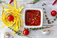 Bowl of homemade tomato sauce, ingredients and pasta on wood - SARF03051