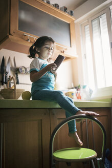 Little girl sitting on kitchen worktop looking at phablet - JASF01278