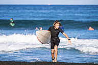 Spain, Tenerife, boy carrying surfboard at the sea - SIPF01004
