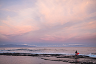 Spain, Tenerife, boy carrying surfboard on the beach at sunset - SIPF01007