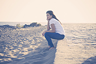 Young woman sitting on the beach - SIPF01014