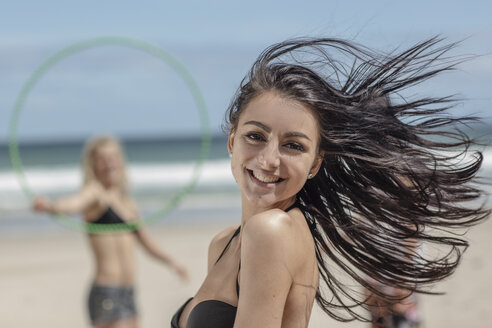 Happy young woman on the beach with friends in background - ZEF11293