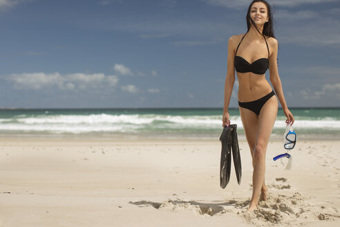 Young woman walking on the beach with snorkeling equipment - ZEF11299