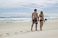 Young couple walking hand in hand on the beach - ZEF11302