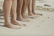 Feet of friends standing on the beach - ZEF11308