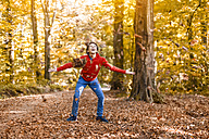 Laughing boy throwing leaves in the air in the autumnal forest - DIGF01399