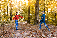 Mother and son throwing with autumn leaves in the forest - DIGF01402