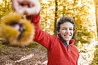 Portrait of smiling boy with sweet chestnut in the autumnal forest - DIGF01417