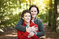 Portrait of smiling mother and son in the autumnal forest - DIGF01420