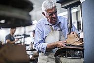 Shoemaker working on shoe in workshop - ZEF11332
