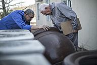 Two men looking at clay jug at industrial pot factory - ZEF11350