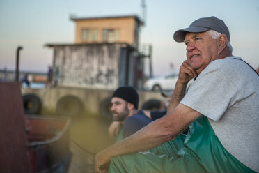 Fishermen sitting in harbour at sunset - ZEF11422