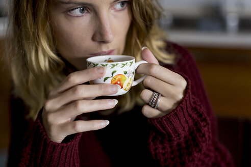 Woman drinking a cup of coffee at home - MAUF00852