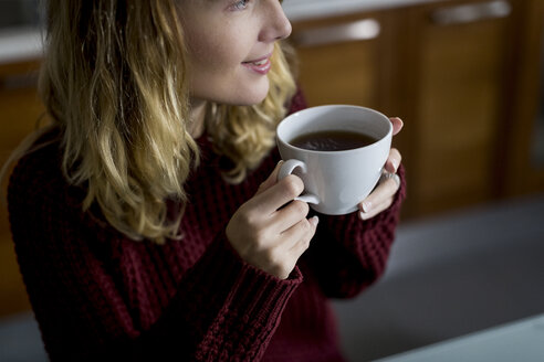 Woman drinking a cup of tea at home - MAUF00855
