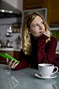 Pensive woman sitting in the kitchen with smartphone and cup of tea - MAUF00858