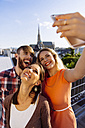 Austria, Vienna, three friends taking selfie on rooftop terrace with Stephansdom in the background - AIF00412
