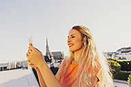 Austria, Vienna, smiling blond woman taking selfie on rooftop terrace with Stephansdom in the background - AIF00418