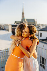 Austria, Vienna, two happy friends embracing on roof terrace with stephansdom in the background - AIF00424