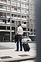 Businessman with suitcase in the city - MAUF00888