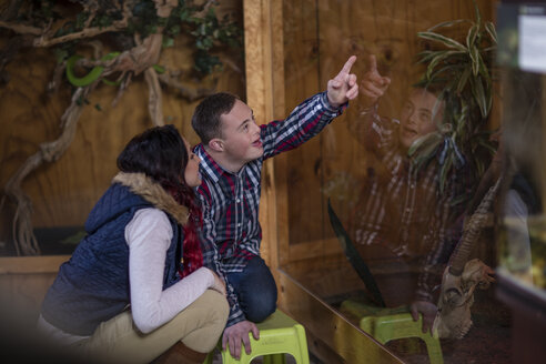 Young man with down syndrome and young woman visiting reptile exhibition - ZEF11488