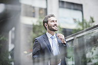 USA, New York City, smiling businessman with earphones - UUF08945