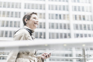USA, New York City, smiling businesswoman on the go with cell phone and earphones - UUF08954