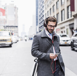 USA, New York City, businessman with cell phone and headphones on the go - UUF08966