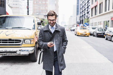 USA, New York City, smiling businessman with cell phone on the go - UUF08969
