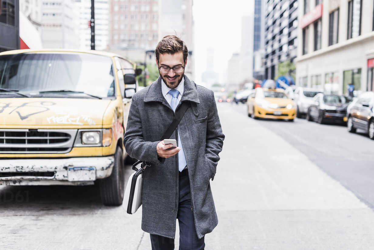 USA, New York City, smiling businessman with cell phone on the go - UUF08969 - Uwe Umstätter/Westend61