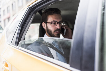 Businessman on cell phone in a taxi - UUF08972