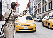 USA, New York City, woman in Manhattan hailing a taxi - UUF08978