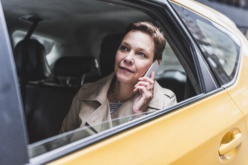 Woman in taxi on cell phone - UUF08984