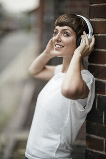 Smiling young woman listening music with white headphones - TAMF00765