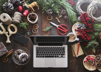 Laptop on desk with working material for Advent wreaths - RTBF00479