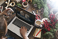 Woman eating bagel while working with laptop, partial view - RTBF00491