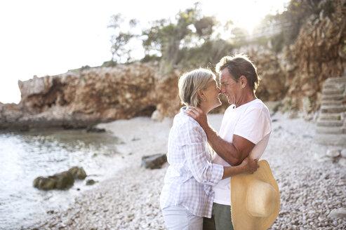 Tender senior couple rubbing noses on the beach - HAPF01025