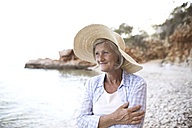Portrait of happy mature woman wearing straw hat on the beach - HAPF01037