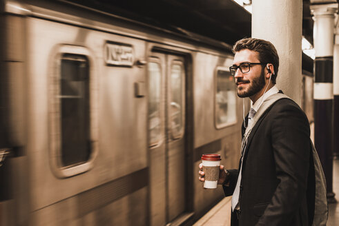 Young businessman waiting at metro station platform, holding disposable cup - UUF08999