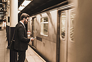 Young businessman waiting at metro station platform, using smart phone - UUF09002