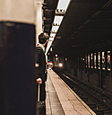 Young businessman waiting at metro station platform - UUF09005
