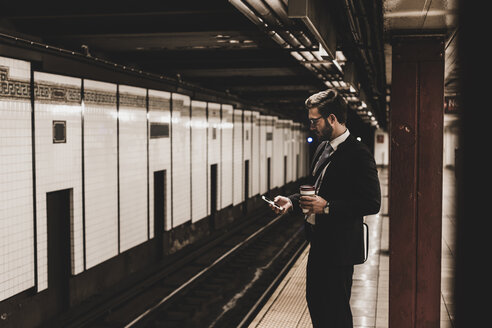 Young businessman waiting at metro station platform, using smart phone - UUF09008