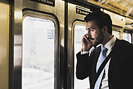 Young businessman taking metro, using smart phone - UUF09011