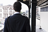 Businessman watching train depart - UUF09014