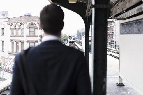 Businessman watching train depart - UUF09014