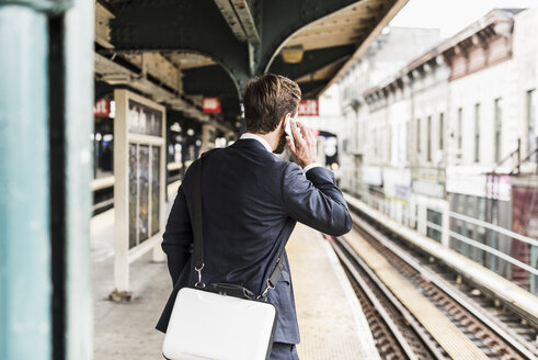 Young businessman waiting at metro station platform, using smart phone - UUF09020